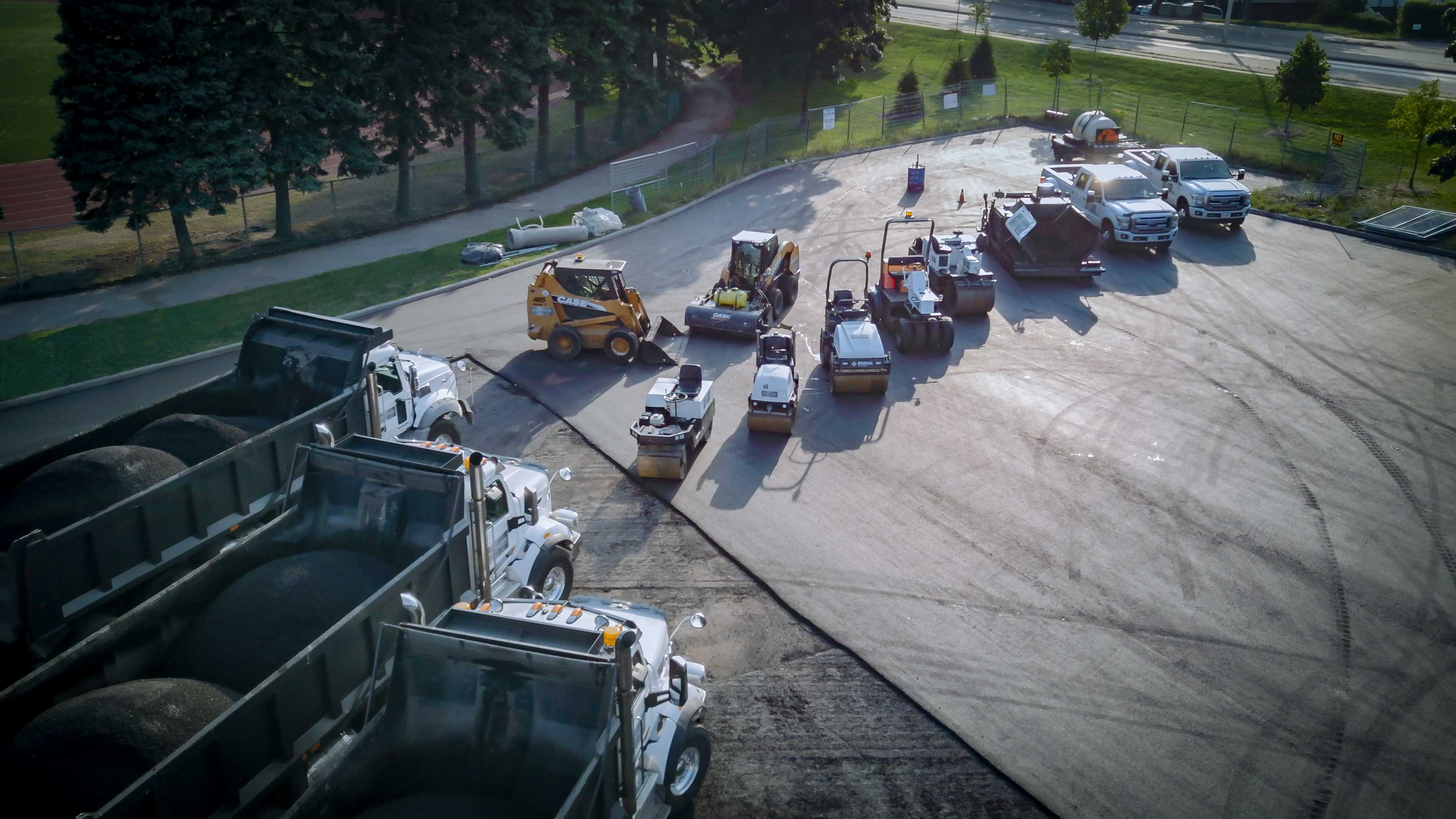 An aerial view of dump trucks and other paving equipment parked in a parking lot.